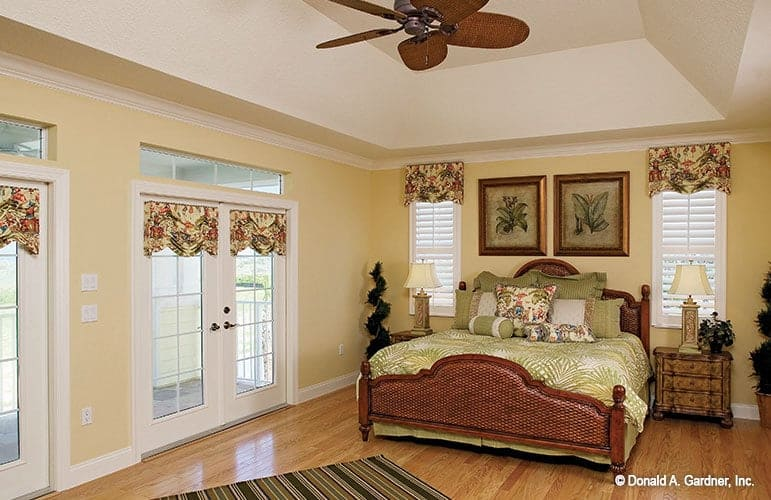 The primary bedroom has a gorgeous tray ceiling, yellows walls, and French doors leading out to the covered porch.