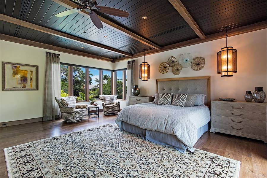 This is the primary bedroom with natural hardwood flooring and a matching wooden beamed ceiling mounted with a fan and ambient pendant lighting flanking the tufted headboard of the bed.