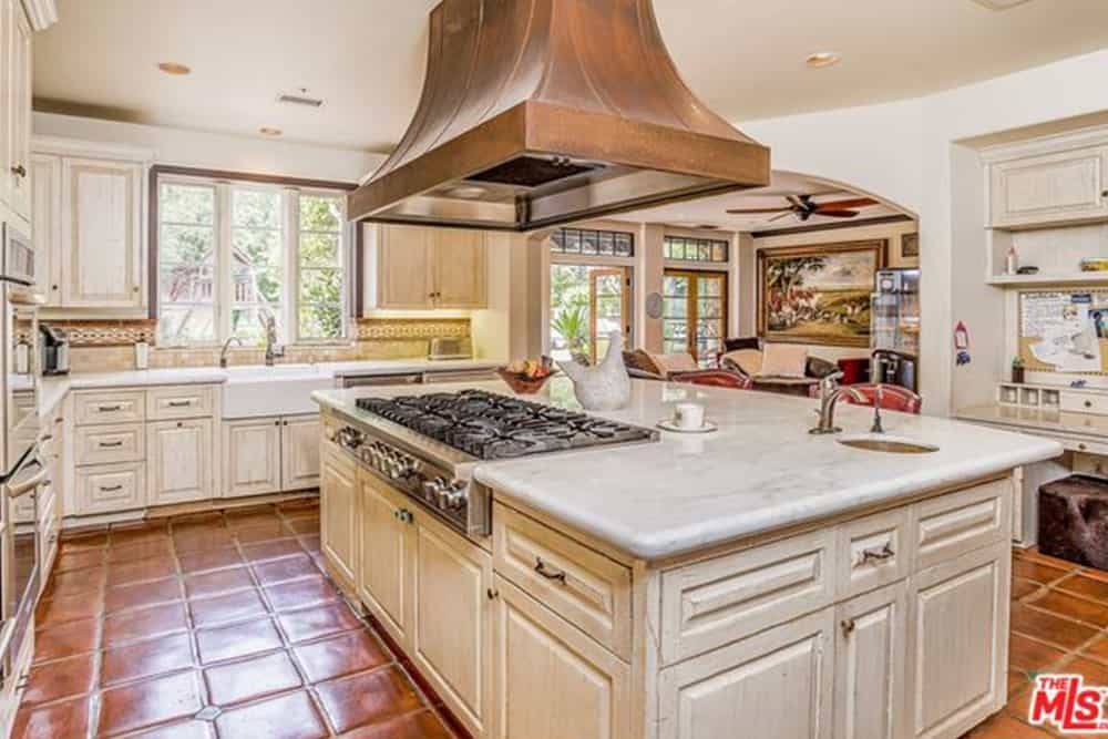 The charming terracotta flooring tiles stand out against the white cabinets and drawers of this Spanish-style kitchen. It has a large kitchen island in the middle that houses the stove-top oven topped with a large vent hood from the white ceiling.
