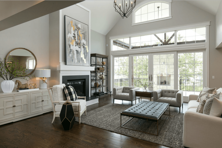 Transitional living room features a high cathedral ceiling and paneled glazing bringing plenty of light in. It has a tufted ottoman with metal legs surrounded by mismatched chairs and couch.