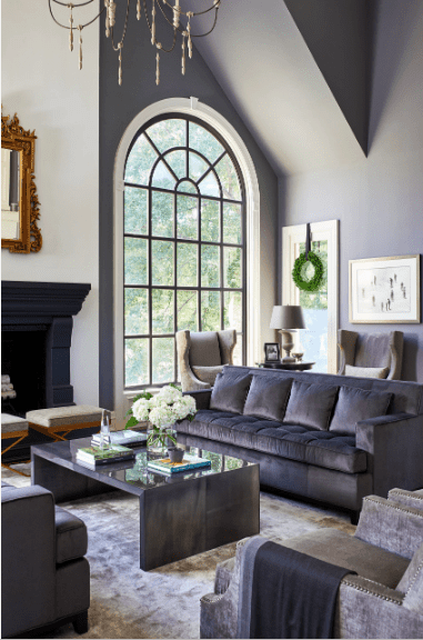 Fabulous living room features an arched window fitted on a gray vaulted wall. It includes a velvet tufted sofa paired with a charcoal coffee table.