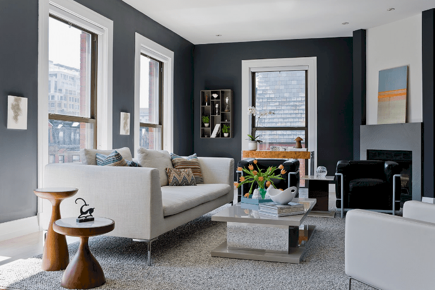 Living room with a charcoal blue wall furnished with mismatched chairs, a marble coffee table and round wooden side tables.