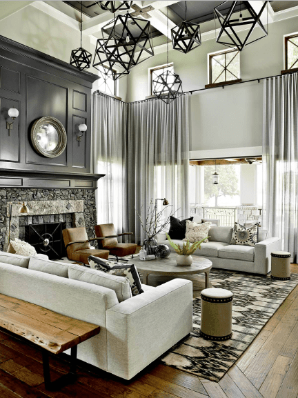 High ceiling living room showcases geometric pendant lights that hung from the coffered ceiling. It has a black wainscoted accent wall fitted with a stone fireplace and round mirror with wall sconces.