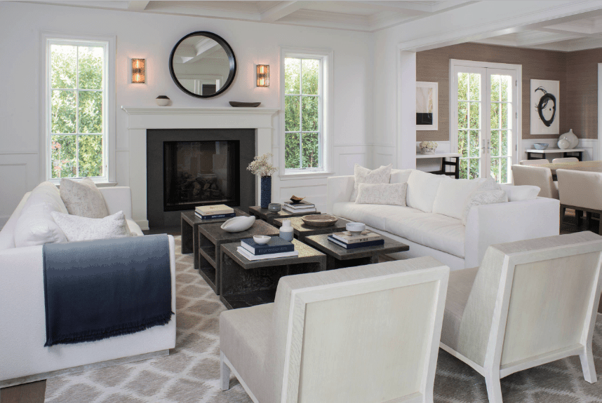 Transitional living room incorporated with a contemporary style. It has a pair of white sectional sofas facing each other along with another pair of gray chairs surrounding a modular coffee table.