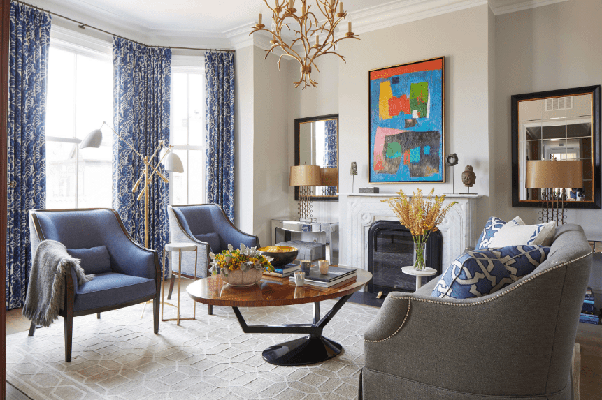 Gorgeous living room designed with a color bursting art piece mounted above the white ornate fireplace. It has glass windows covered with beautiful blue printed draperies with bronze hardware.