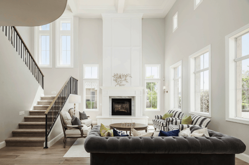 Transitional living room surrounded with white framed glass windows and covered with coffered ceiling. It has a wainscoted pillar fixed with a fireplace with gray marble surround tiles.