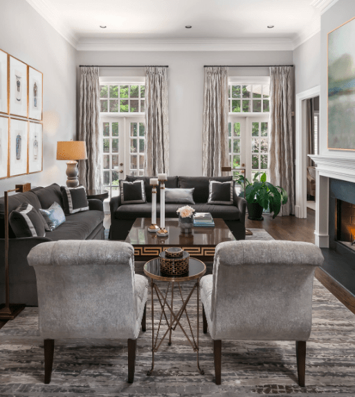 This living room features a pair of French doors covered with patterned curtains. It includes matching black sofas and gray armchairs sitting on a contemporary rug over hardwood flooring.