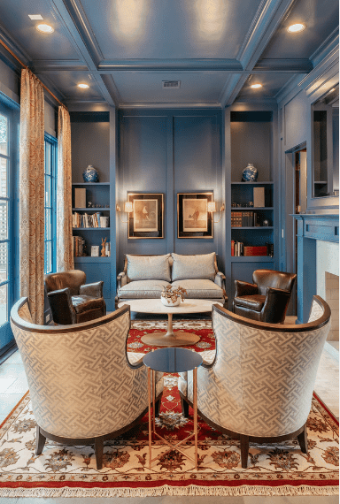 Blue living room with a round coffee table in the middle that sits on a red fringed rug. It is surrounded by a gray loveseat along with a pair of leather and wingback chairs.