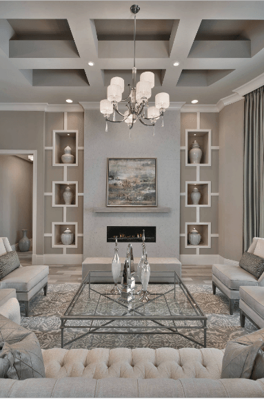 Luxurious living room decorated with classy vases and a lovely wall art piece mounted above the modern fireplace. It is illuminated by a fancy chandelier that hung from the coffered ceiling.
