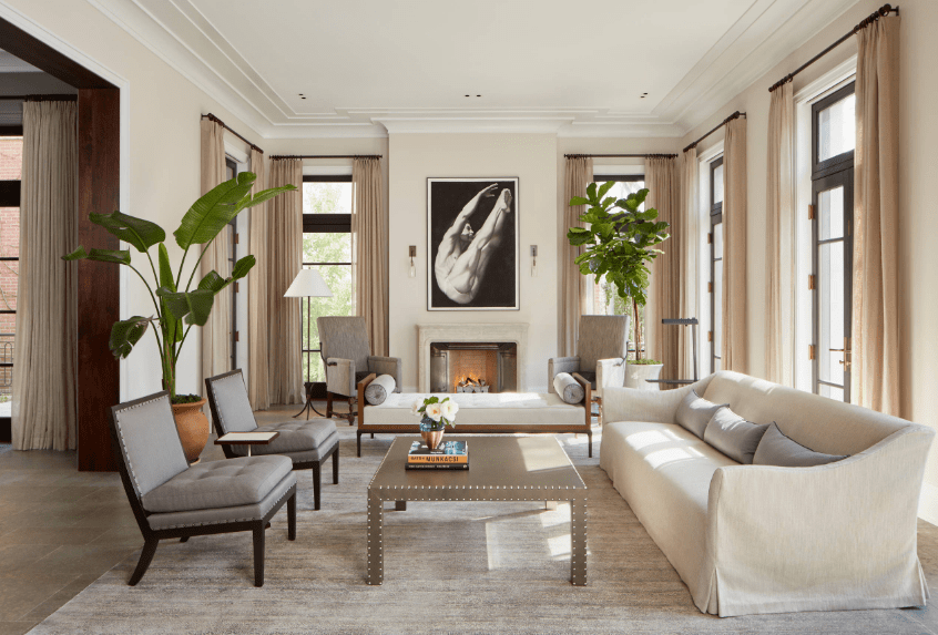 The fresh living room features a floor to ceiling glass windows wrapped with sheer curtains. It has a banana and fiddle leaf fig plant that creates a tropical feel to the area.