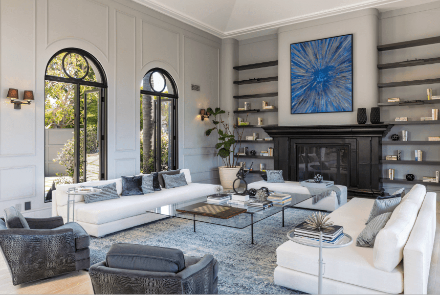 Stylish living room showcases wainscoted walls fitted with arched glass windows. It includes a black fireplace below a blue sunburst painting and in between gray wall filled with floating shelves.