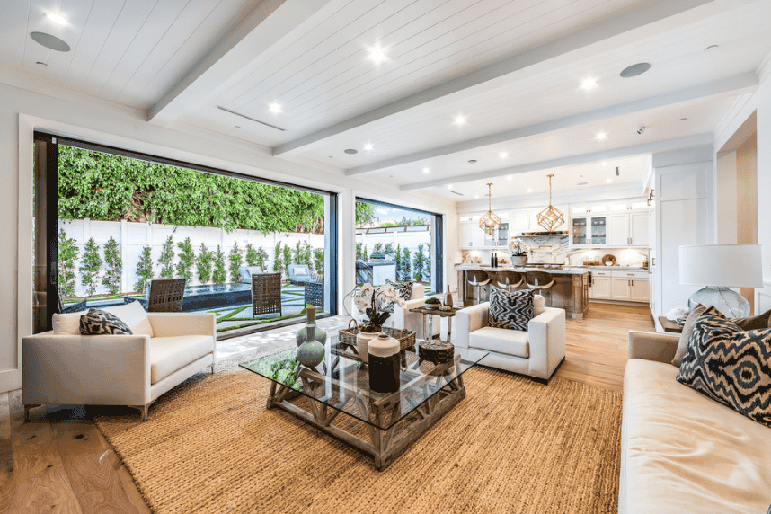An expansive living room boasts a glass top wood coffee table that sits on a woven rug. It has panoramic windows with an amazing outdoor pool view.