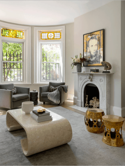An interesting portrait is mounted above the concrete fireplace in this taupe living room. It is filled with gray armchairs and brass stools along with a marble coffee table.