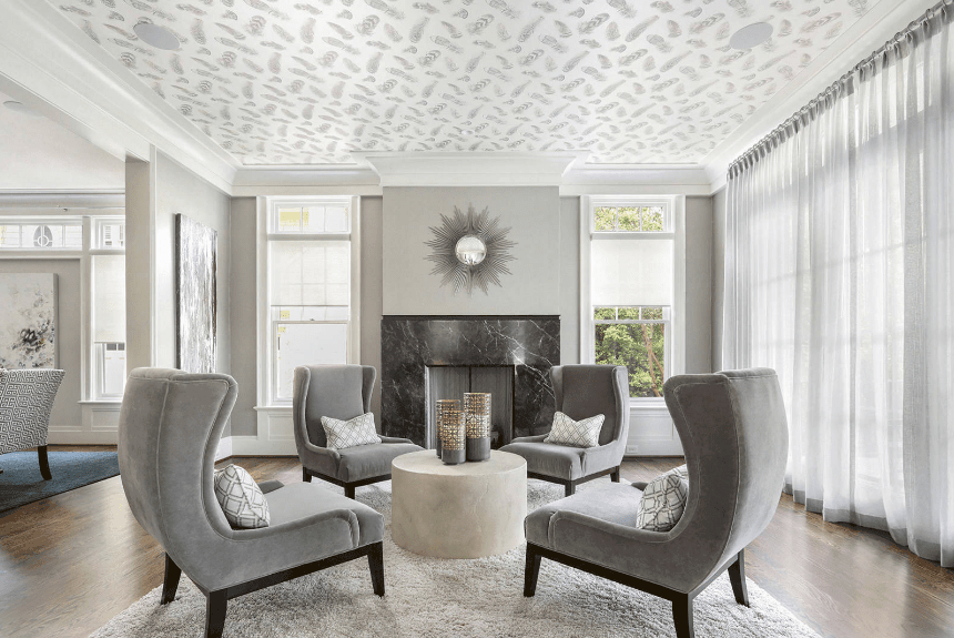 Elegant living room showcases gray wingback chairs surrounding a round center table. It has a sunburst mirror mounted above a black marble fireplace.