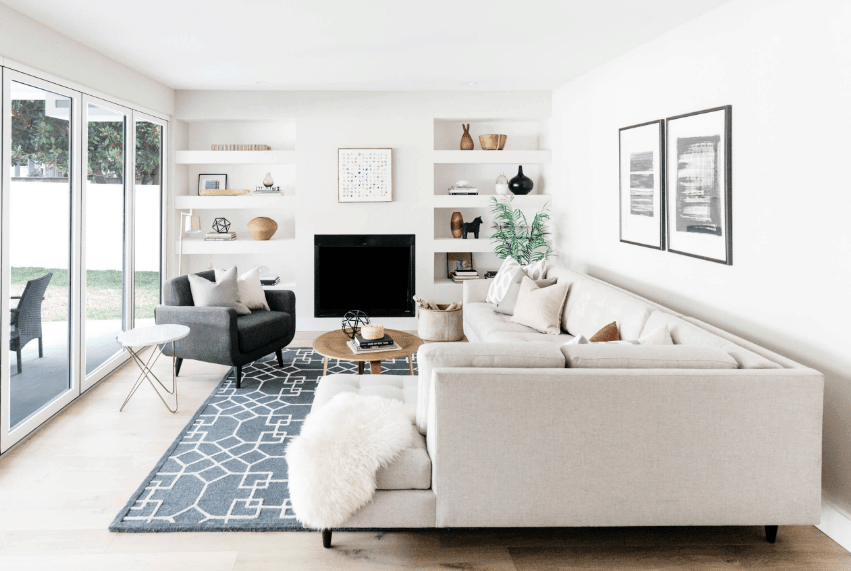 Clean white living room beautifully contrasted with a black armchair and geometric rug. It has an L-shaped sectional sofa paired with a wooden coffee table.