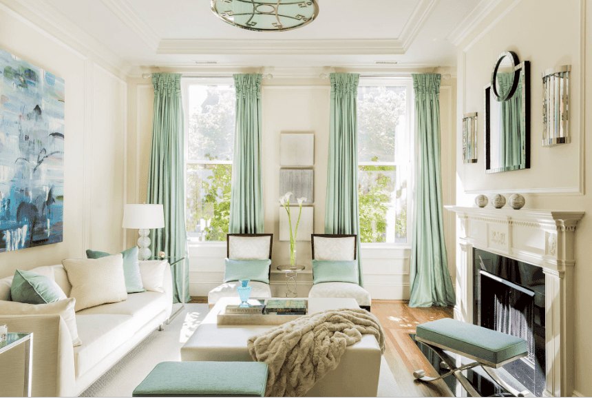 Charming living room with a pop of green color from the curtains, throw pillows and metal stools. It has a lovely wall art piece mounted above the white couch.