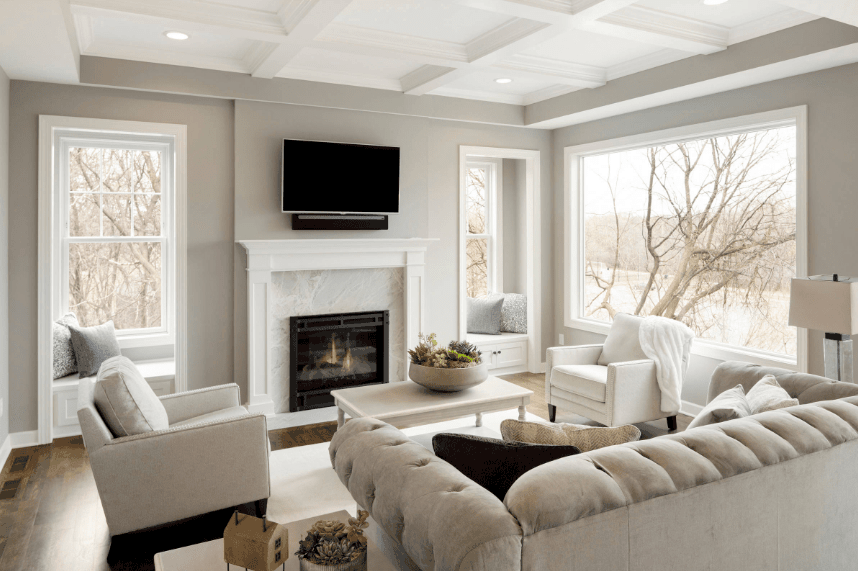 Bright living room with a picture window that overlooks the outdoor view. It has white seat nooks with built-in storages accented with gray pillows beneath framed windows.