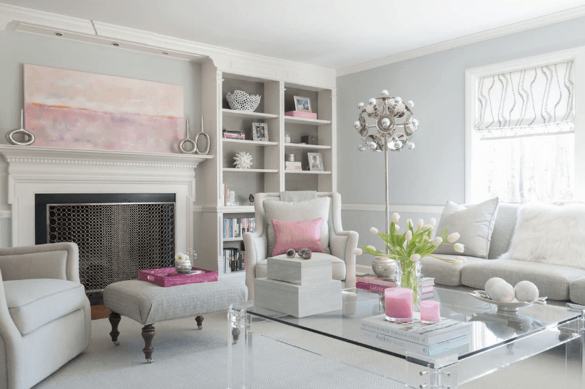Gorgeous living room boasts a calming neutral color palette accented with pops of pink. It has gray wingback chairs and a sectional sofa lighted by a stylish floor lamp.