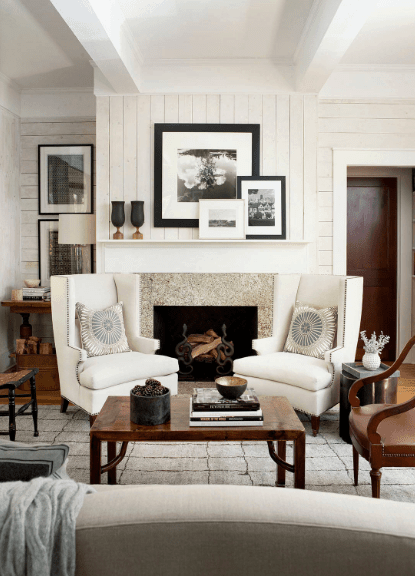 A pair of white wingback chairs sit in front of a white fireplace fixed into the shiplap wall designed with black and white frames.