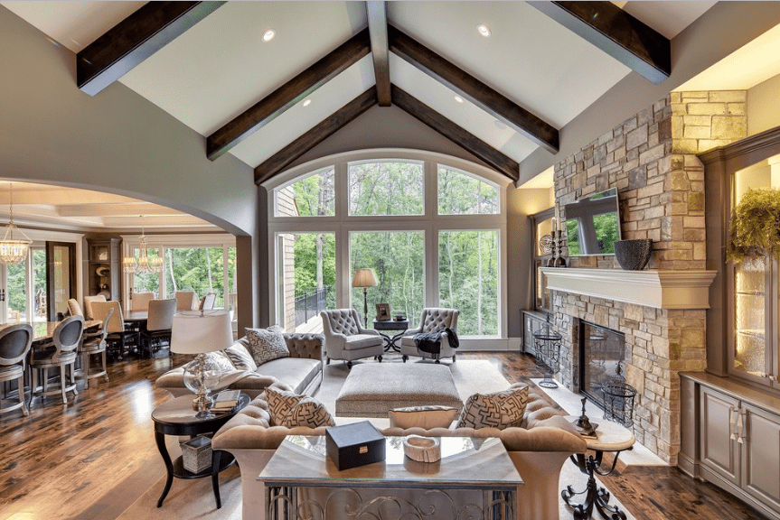 Cozy living room features a cathedral ceiling with exposed wood beams. It has arched glazed windows overlooking the enchanting forest view.