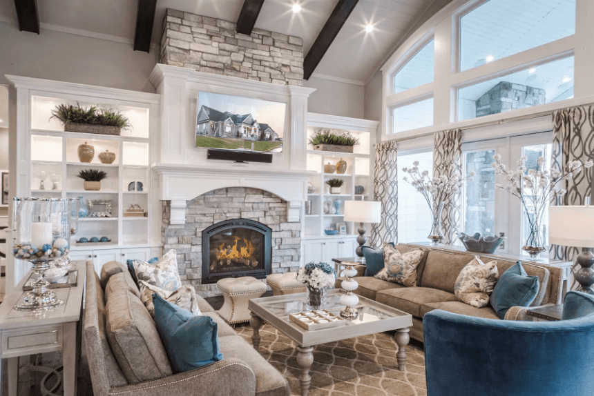 This living room offers a brick fireplace with tufted stools in front of it. It also includes facing sectionals and a glass top coffee table over a beige patterned rug