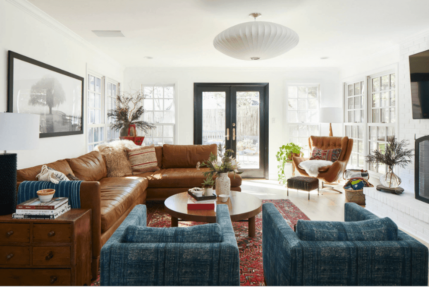 A white round chandelier hung over an L-shaped leather sofa, a pair of blue armchairs and a wooden coffee table along with a brown tufted accent chair in this white living room.