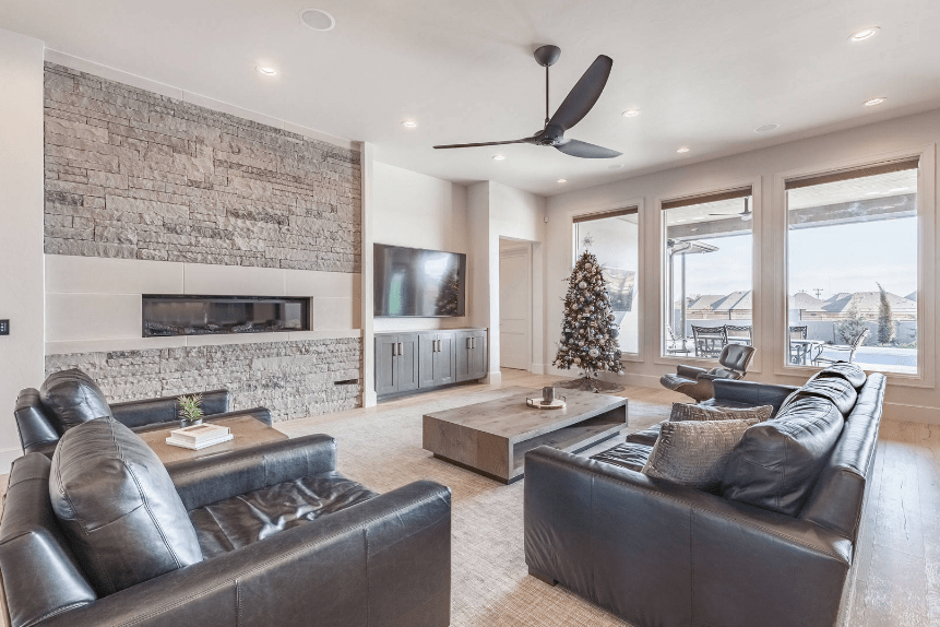 Classy living room showcases a modern fireplace with marble surround tiles fixed to a stone accent wall. There's a television beside it mounted above built-in cabinets.