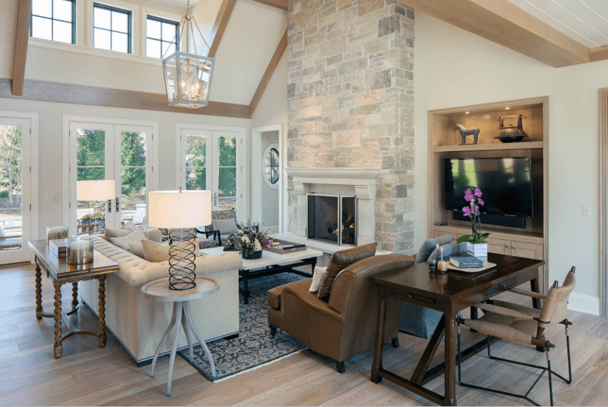 Transitional living room features a stone brick pillar fitted with a fireplace and lined with beige mantel. It includes a wooden desk and table placed behind the armchairs and tufted sofa.