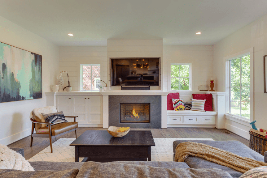 This living room showcases a white shiplap accent wall fixed with a fireplace in between a built-in cabinet and window seat nook styled with multi-colored pillows.