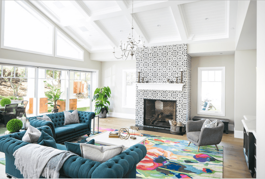 Artsy living room boasts teal adjacent sofas paired with a white coffee table and gray accent chair over a colorful rug.