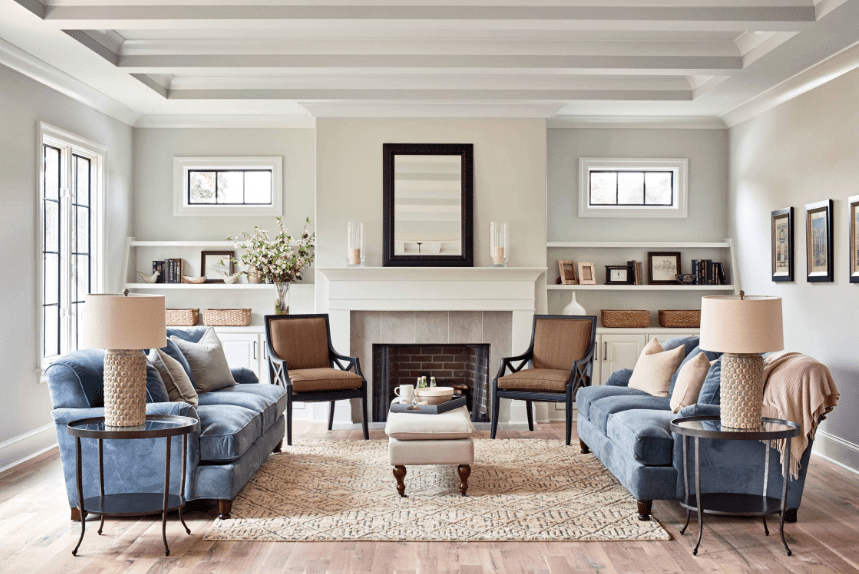 Symmetrical living room features a small beige ottoman with wooden legs as the focal point. It is accompanied by a pair of brown chairs, blue velvet facing sofas and round glass top side tables.