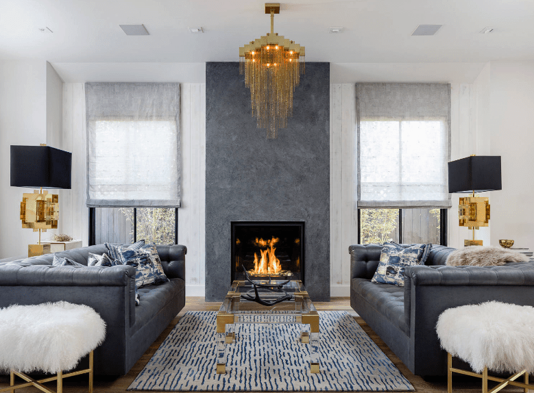 The luxurious living room showcases a glass coffee table with matching tufted sofas and faux fur stools on the sides. It is lighted by a gorgeous chandelier and a pair of black modern table lamps.