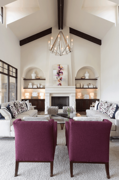 Charming living room with a cathedral ceiling lined with dark wood beams. It has arched walls fitted with wooden floating shelves and built-in cabinets.