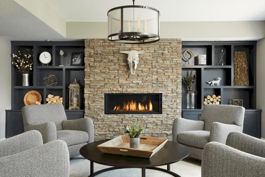 Elegant living room with a modern fireplace fixed on a brick stone wall in between black built-in shelves. It is illuminated by a drum chandelier that hung over a round coffee table surrounded by gray armchairs.