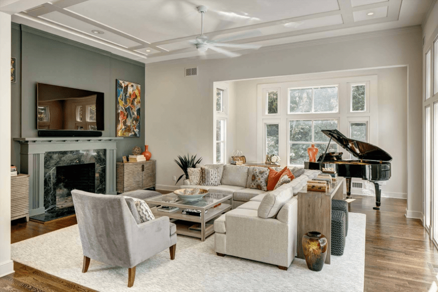 Transitional living room with a gray velvet chair and beige L-shaped sectional accompanied by a baby grand piano.