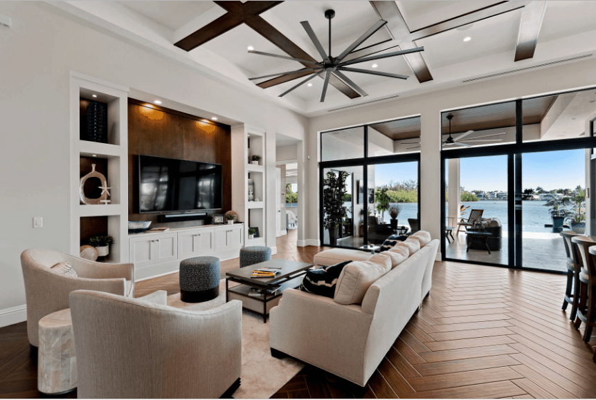 White living room showcases coffered ceiling and herringbone wood flooring. It also has glazed windows that allow plenty of light in.