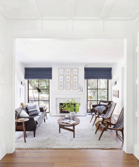White living room offers paneled glass windows covered with deep blue roman shades. It has a fireplace at the center designed with gallery frames.