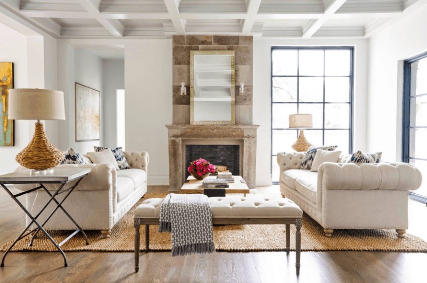 This living room showcases a tufted bench that matches with the facing sofas over a woven rug. It is styled with a rectangular mirror that lays on the brick accent wall lighted by sconces.