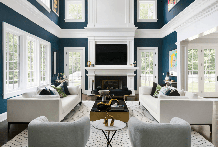 High ceiling living room boasts dark blue walls accented by white crown moldings and filled with white framed glass windows.