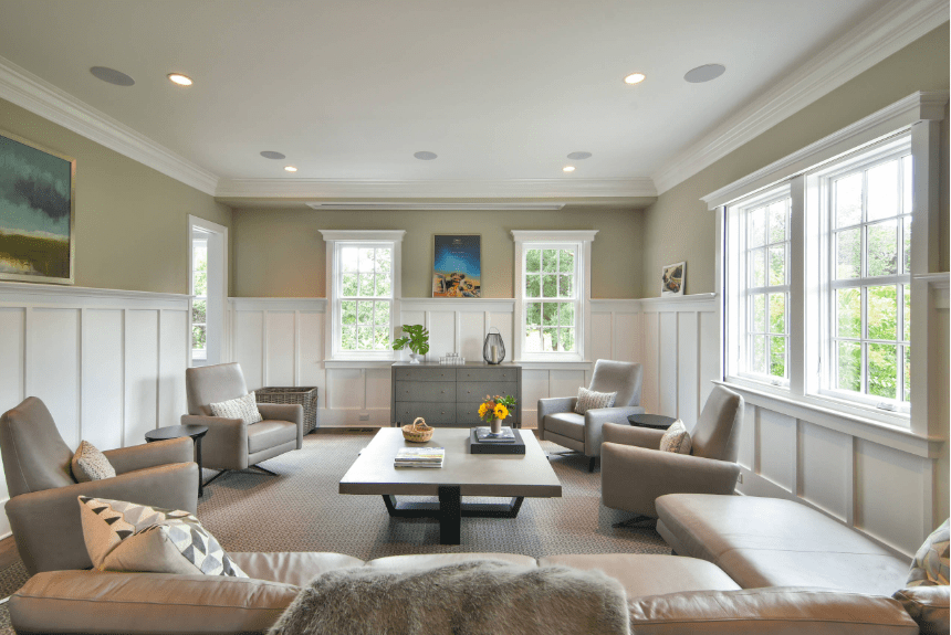 Simple living room with an L-shaped sectional sofa and leather armchairs surrounding a coffee table. It has taupe walls above white wainscoting.