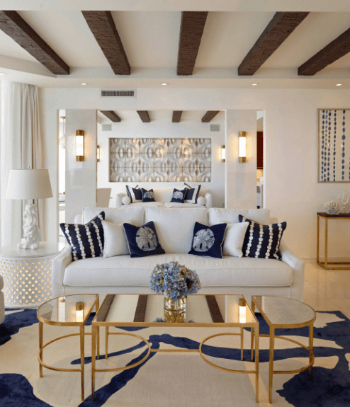 Fabulous living room features a white sofa accented with blue and white pillows. It is paired with a classy modular coffee table over a printed rug.