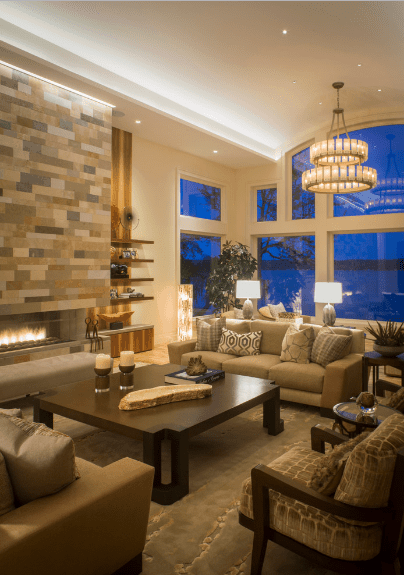 Elegant living room boasts a brick accent wall fitted with a fireplace. It is illuminated by table lamps and a chandelier that hung from the arched ceiling.