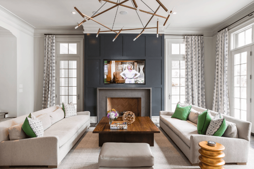 Transitional living room showcases gray facing sofas along with leather stool and wooden coffee table. It is lighted by a statement chandelier and natural light that flows through the glass windows.