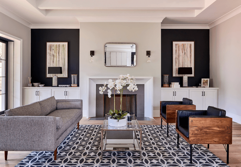 Modern living room accented with a striking patterned rug along with black walls decorated by wall arts. It includes a beveled mirror illuminated by clear glass sconces.