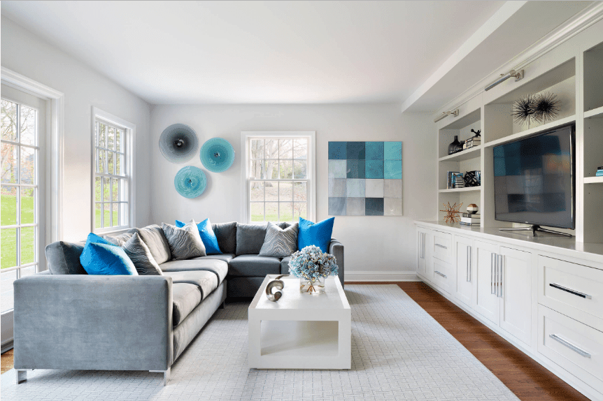 Airy living room styled with lovely round and checkered blue wall arts. It has an L-shaped sectional with white coffee table over gray rug.