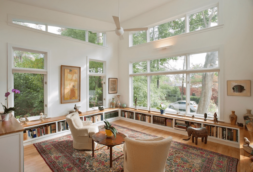 Glazed living room features built-in bookshelves beneath the windows overlooking the serene outdoor greenery.