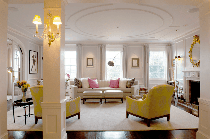 Charming living room accented with yellow armchairs and gold round mirror fitted above the ornate fireplace.