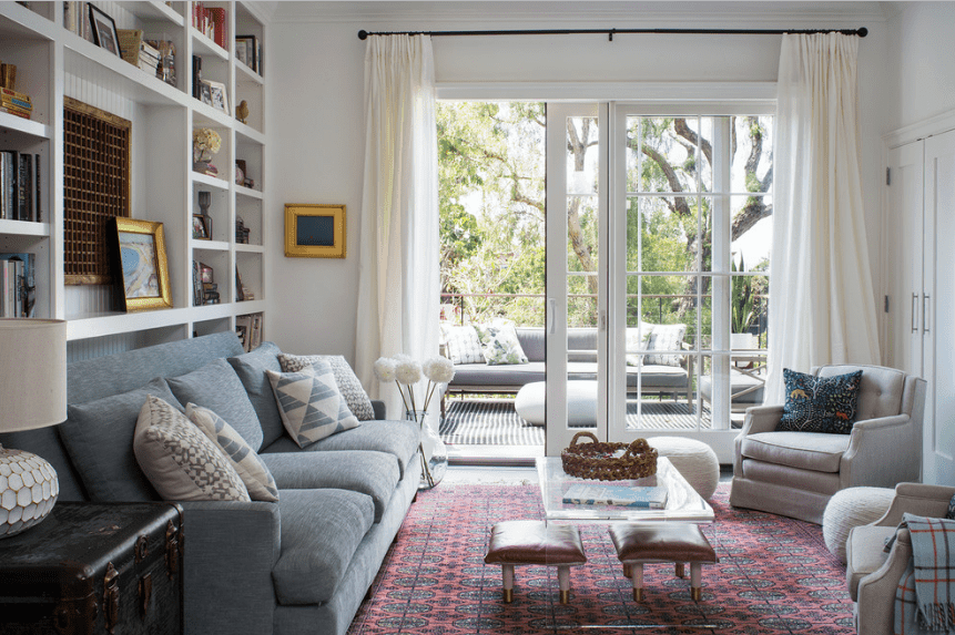 A gray sectional sofa rests on the white built-in shelves in this living room. It includes a glass coffee table with stools and a pair of tufted gray chairs that sit on a vintage rug.