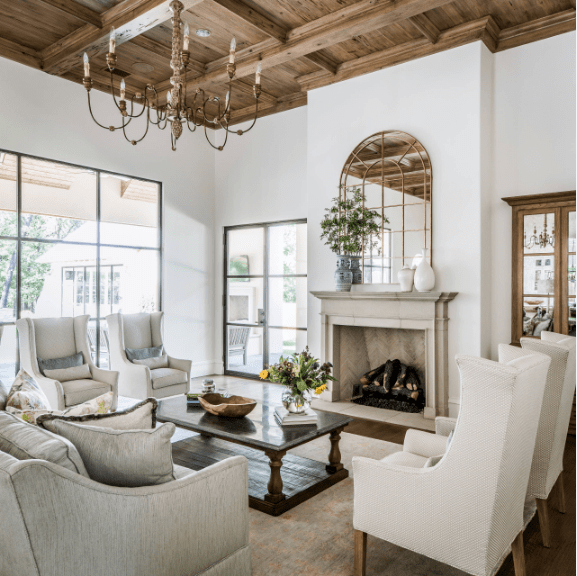 Bright living room features a wooden coffered ceiling with a hanging vintage chandelier. It is surrounded by glass windows allowing plenty of light in.