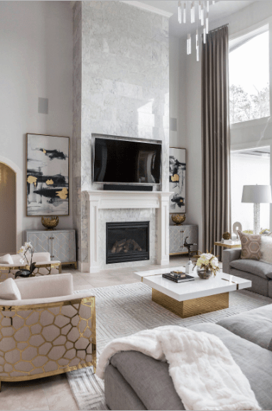 The glam living room showcases a glossy stone brick pillar fixed with a fireplace that's topped with a television. It has a gold coffee table with white marble top that complements with the modern chairs framed with gold patterns.